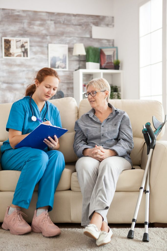 Female doctor with senior woman sitting on couch